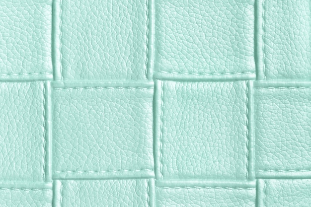 Texture of light blue and cyan leather background with square pattern and stitch, macro.