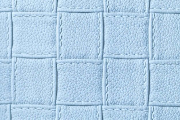 Texture of light blue leather background with square pattern and stitch, macro.