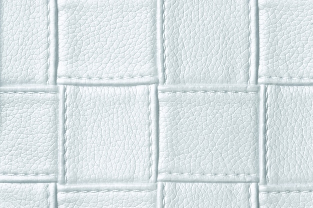 Texture of light blue leather background with square pattern and stitch