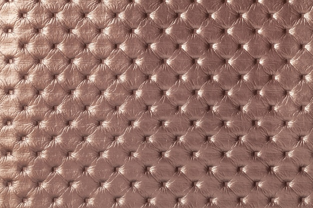 Texture of light brown leather background with capitone pattern, macro. bronze textile of retro chesterfield style. vintage fabric.