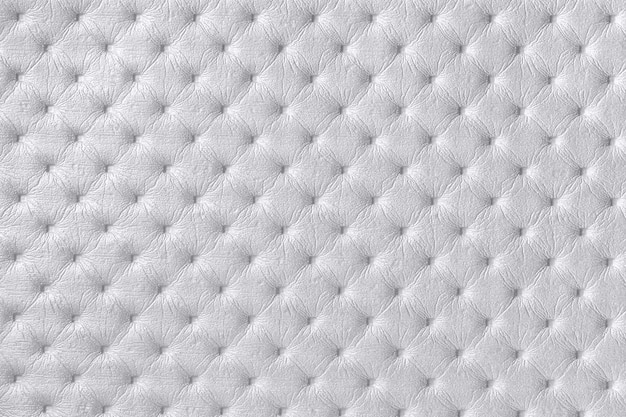 Texture of light gray and silver leather fabric background with capitone pattern, macro. textile of chesterfield style.