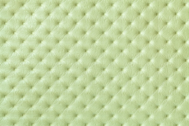 Texture of light green leather background with capitone pattern, macro