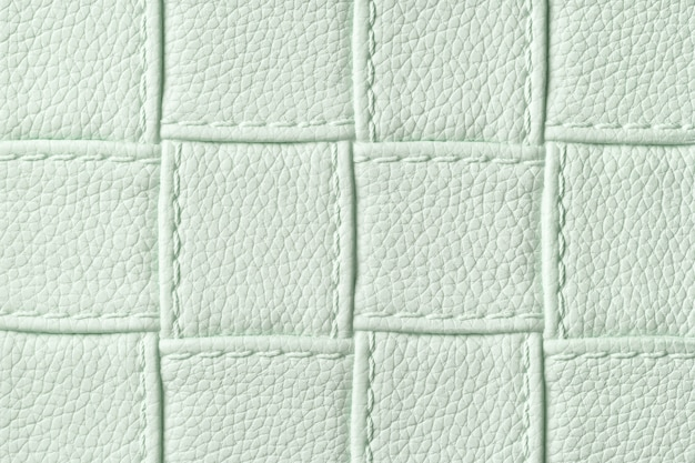 Texture of light green leather textile background with square pattern and stitch.