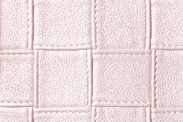 Texture of light pink leather background with square pattern and stitch