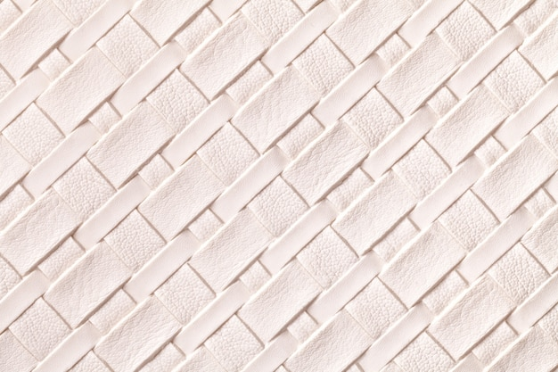 Texture of light pink leather background with wicker pattern, macro.