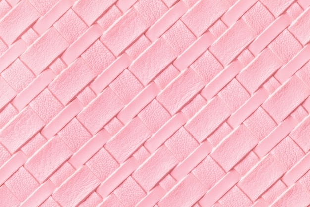 Texture of light pink leather background with wicker pattern