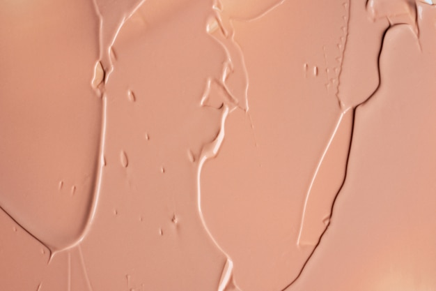 The texture of liquid beige foundation blur cream background of make up. acrylic smears.