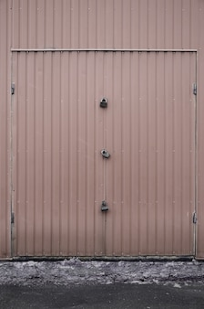 Texture of a metal brown wall with a gate closed for three locks