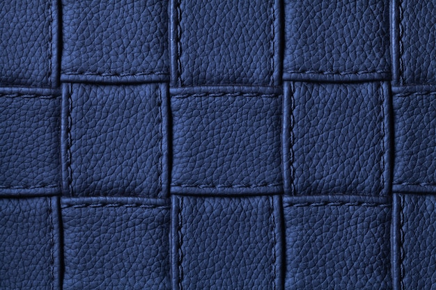 Texture of navy blue leather background with square pattern and stitch, macro. abstract from modern decorative dark indigo textile with geometric shape.