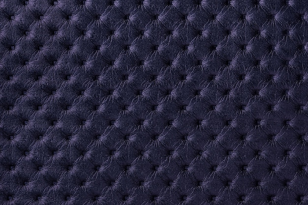 Texture of navy blue leather fabric background with capitone pattern. dark purple textile of retro chesterfield style.