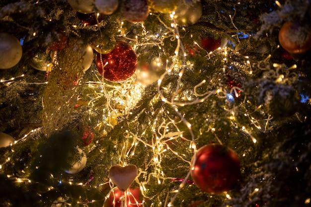 장식용 볼 장난감과 빛나는 화환이 있는 크리스마스 트리 분기의 질감 새해 근접 촬영