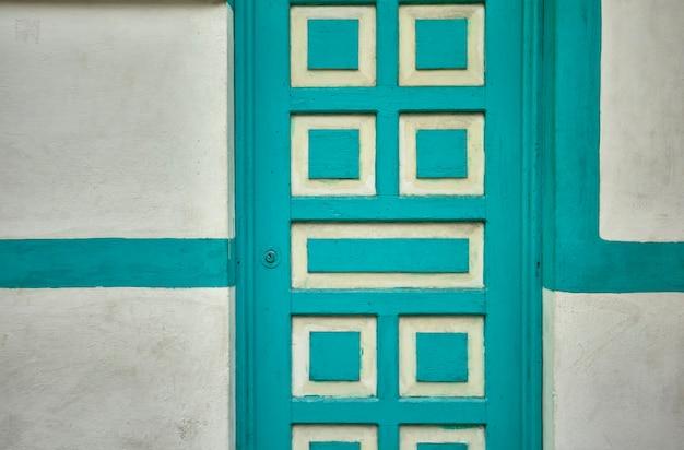 Текстура детали белой двери с синими деталями.