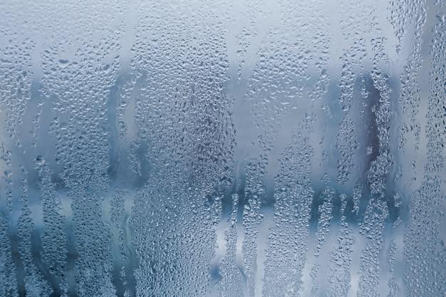たくさんの水滴と結露が流れる霧のかかったガラスの質感。