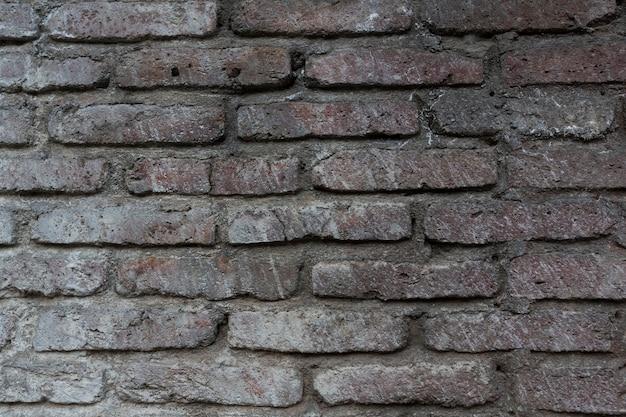 古い生のレンガで作られた壁の質感。壁は濃い灰色です。高品質の写真