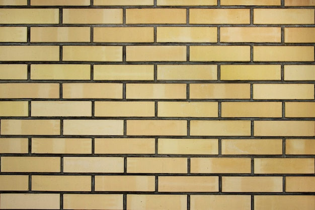 田舎の黄色いレンガの壁の背景のテクスチャ、石の粗いブロック、レンガ組積造の水平色技術アーキテクチャの壁紙。レンガの黄色い壁。