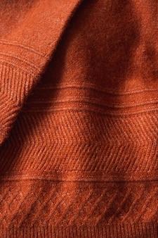 Текстура осеннего вязаного свитера с узором. осенний уютный фон.