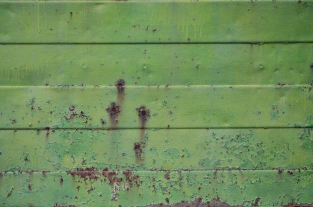 大きな損傷を受けた古い緑色の金属製の壁のテクスチャ