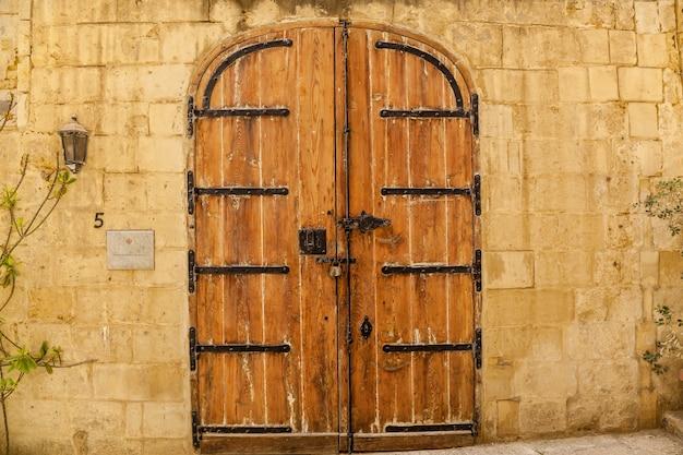 Текстура старой деревянной деревянной двери с необычными металлическими ручками на острове мальта
