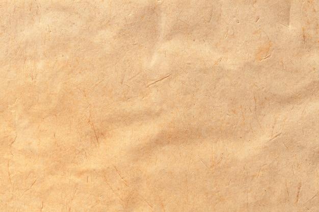 ベージュの古い紙の質感、しわくちゃの背景。ヴィンテージブラウンの表面。クラフトダンボールの構造。