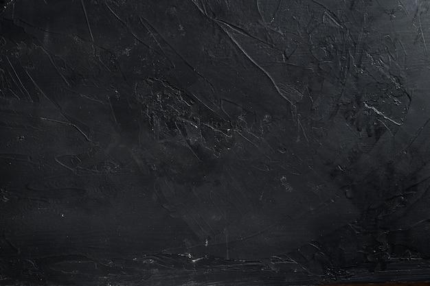 黒いコンクリートの壁の詳細のテクスチャ