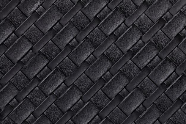 Текстура черной кожи фона с плетеным узором, макрос. абстракция из современного декоративного текстиля с диагональными линиями.
