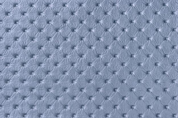 キャピトンパターンと青い革生地の背景のテクスチャ。レトロなチェスターフィールドスタイルのデニムテキスタイル。