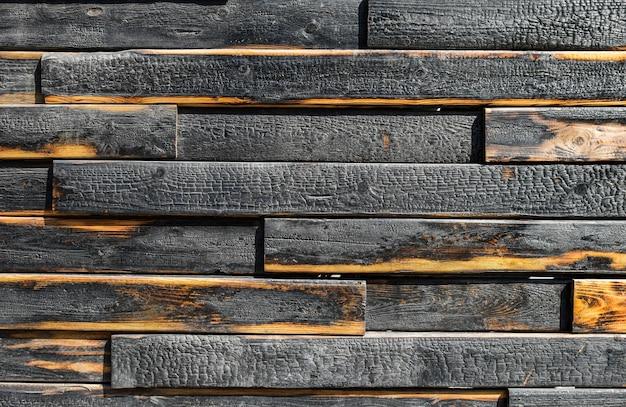 焦げた板の質感。明るい静脈のある黒くなった焦げた木の板。焦げた傷のある広葉樹の表面。