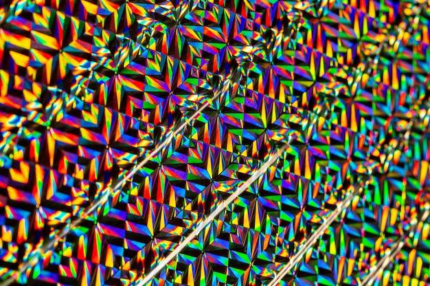 ホログラフィック効果のある色付きホイルのテクスチャ。クリスマス、新年、休日、お祭り、カーニバルの背景