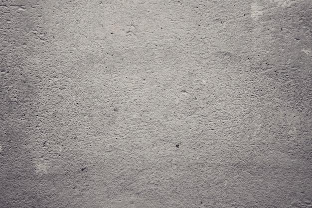 壁のコンクリートと漆喰の質感。しっくいの波線。装飾的なしっくいやスタッコのテクスチャがクローズアップ、抽象的な灰色の背景。