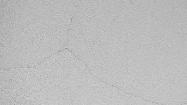 Текстура трещины белой цементной стены - фон