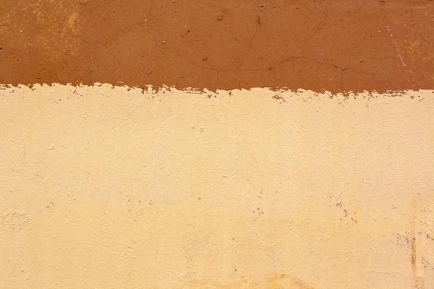 Текстура треснувшей старой оштукатуренной стены разделена на желтый и коричневый цвета двух цветов. много трещин и царапин. скопируйте пространство.
