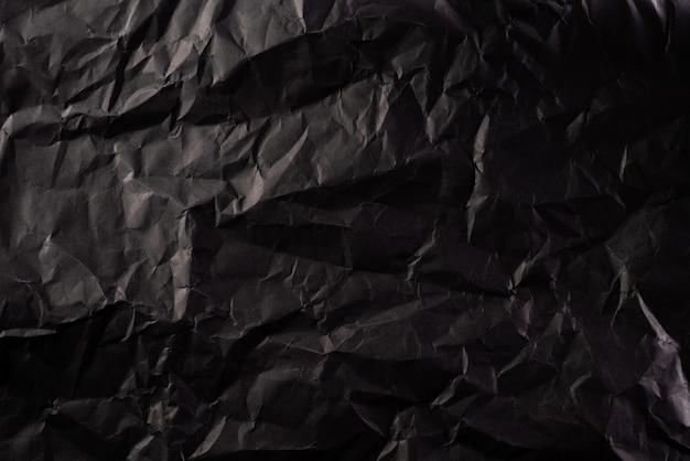 しわくちゃの黒い紙のテクスチャ。創造的なビンテージ背景。