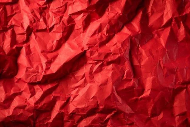 しわくちゃの赤い紙のテクスチャ。デザインの背景の創造的なヴィンテージ。