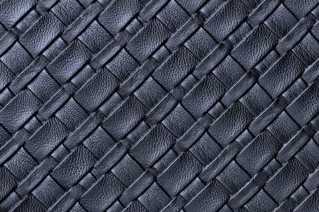 Текстура темно-синего кожаного тканевого фона с плетеным узором, макросом.