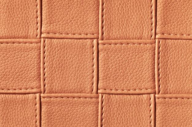 正方形のパターンとステッチで濃いオレンジと赤の革の背景のテクスチャ