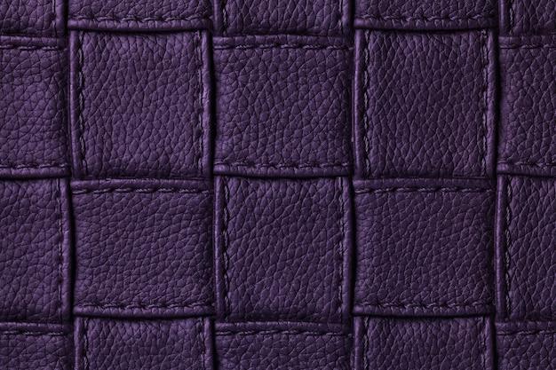 正方形のデザインとステッチ、マクロで濃い紫色の革の背景のテクスチャ。
