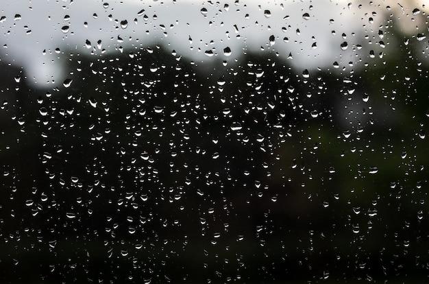 暗いガラスの上の雨滴のテクスチャ