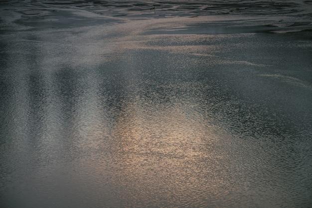 日の出の湖の黄金の穏やかな水の質感。水面の瞑想的な波紋。日没時の金の湖の自然の最小限の背景。澄んだ水の自然な背景。湖の断片のフルフレーム。