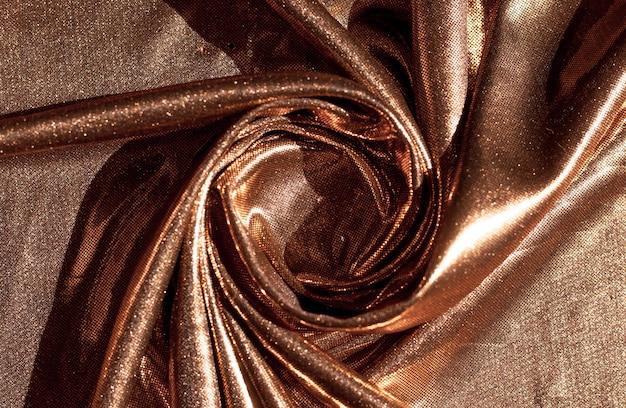 Текстура золотой ткани в волнах, фон