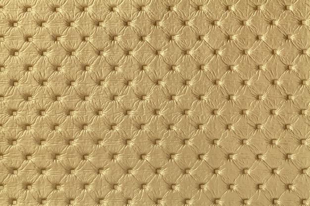 Текстура золотой кожаной ткани фона с рисунком капитоне. желтая ткань в стиле ретро честерфилд.