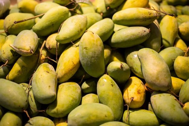 녹색 육즙이 신선한 망고 과일의 질감. 판매를 위한 신선한 녹색 망고 그룹입니다. 태국 과일 열대 생망고입니다. 열대와 이국적인 과일.
