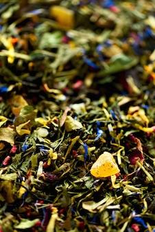 青い花、カレンデュラ、コーンフラワーの乾燥花びらと緑茶のテクスチャ。フード。有機性健康的なハーブの葉、デトックスティー。