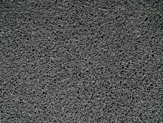 Текстура переплетенных пластиковых нитей, используемых в коврах