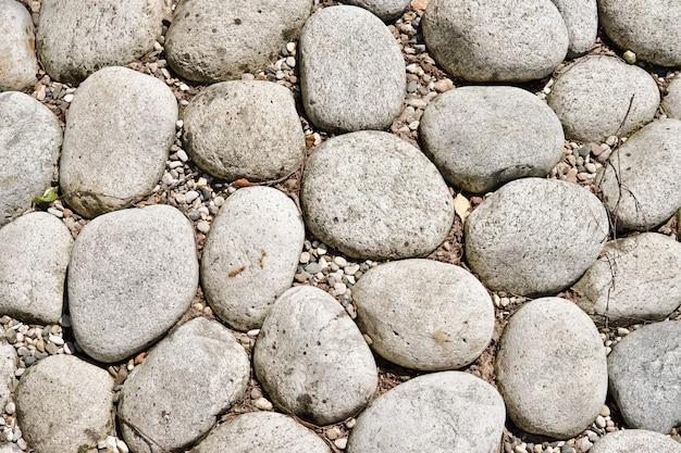 Фактура из крупных гладких камней, декоративно выложенных на земле. фрагмент ландшафтного дизайна. абстрактный фон.