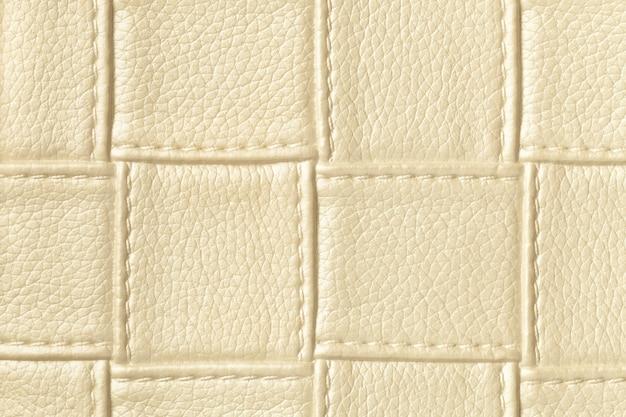 正方形のパターンとステッチでライトゴールデンとクリーム色の革の表面のテクスチャ
