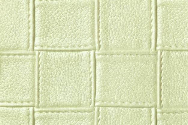 正方形のパターンとステッチ、マクロと薄緑色の革の背景のテクスチャ。