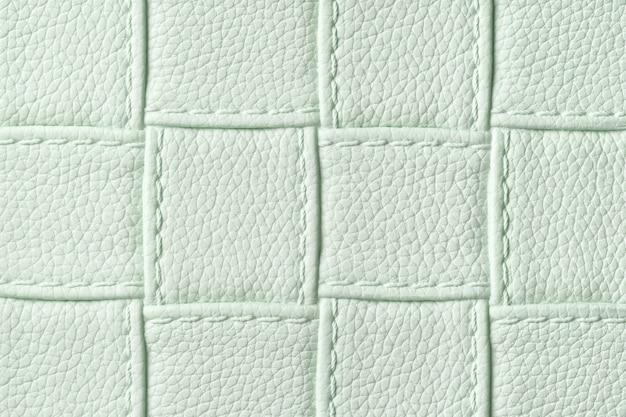 正方形のパターンとステッチのライトグリーンレザーテキスタイル背景のテクスチャ。