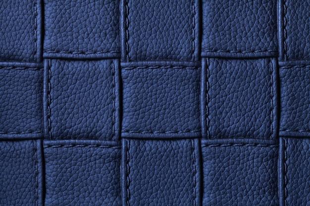正方形のパターンとステッチ、マクロとネイビーブルーの革の背景のテクスチャ。幾何学的な形をしたモダンな装飾的なダークインディゴテキスタイルからの抽象。