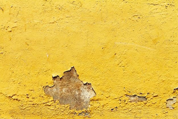 古いアンティークのヴィンテージテクスチャ黄色の壁がひび割れ。閉じる。