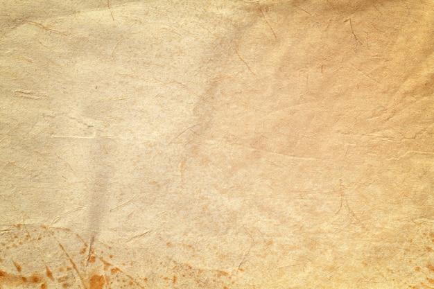 コーヒーの染み、しわくちゃの背景を持つ古いベージュの紙の質感。ヴィンテージブラウングランジ表面背景。